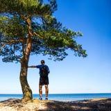 远足概念-有背包的人在海滩 免版税库存照片