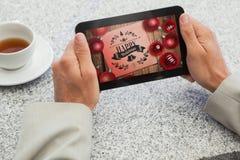 Составное изображение бизнесмена держа малую таблетку на таблице Стоковые Фотографии RF
