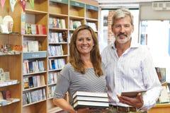 书店男性和女性业主使用数字式片剂的 免版税库存照片