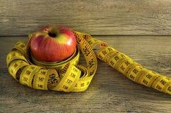 在苹果附近被包裹的测量的磁带 免版税图库摄影
