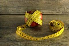 在苹果附近被包裹的测量的磁带 免版税库存图片