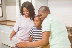 компьтер-книжка семьи счастливая используя Стоковая Фотография