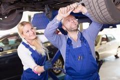 工作在汽车修理店的技工和助理 库存照片