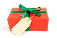 小红色圣诞节或生日礼物与绿色丝带弓、礼物标记或者标签,隔绝在白色背景 免版税库存图片