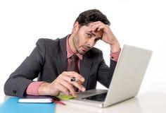 在研究计算机膝上型计算机的办公桌的可爱的商人看起来疲乏和繁忙 库存图片