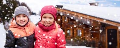 Ευτυχές κορίτσι που αγκαλιάζει το αγόρι πέρα από το εξοχικό σπίτι και το χιόνι Στοκ εικόνες με δικαίωμα ελεύθερης χρήσης
