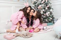 有两个女孩的少妇在礼物和玩具中的圣诞树附近 免版税库存照片