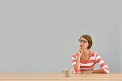 Молодая стильная женщина сидя на изолированном столе Стоковые Фотографии RF