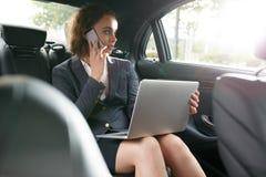 坐在旅馆大厅的商人使用手机和膝上型计算机 免版税库存照片