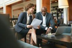 坐在旅馆大厅的商人使用手机和膝上型计算机 免版税图库摄影