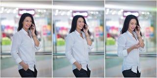 可爱的妇女发表演讲关于在购物中心的机动性 摆在现代购物中心的白色男性衬衣的美丽的时兴的女孩 库存照片