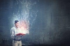 Закройте вверх книги человека раскрытой удерживанием Стоковая Фотография