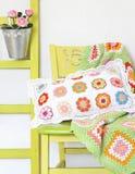 手工制造枕头和毯子在椅子 免版税库存照片