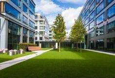 有绿色草坪、树和长凳的现代办公室停车场 免版税库存照片