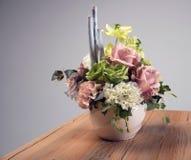 在花瓶的人造花花束在桌上 免版税库存图片