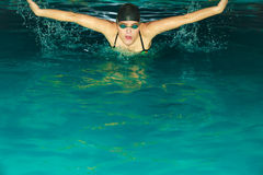 Κτύπημα πεταλούδων κολύμβησης αθλητών γυναικών στη λίμνη Στοκ Φωτογραφία
