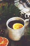 冬天饮料用柠檬和蔓越桔在金属杯子和舒适被检查的格子花呢披肩 库存图片