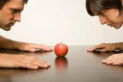 凝视苹果的夫妇 免版税库存照片