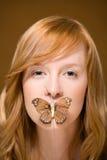 蝴蝶覆盖物妇女的嘴 库存图片