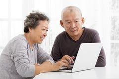 使用膝上型计算机的资深夫妇在客厅 免版税图库摄影