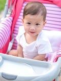 在婴儿推车的亚洲女婴微笑和看起来快乐的开会 免版税库存照片