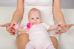 妈妈在她的膝盖和拿着投入了一个两个月婴孩他的笔 图库摄影