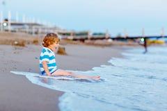 获得愉快的小孩的男孩与沙子城堡的乐趣 库存照片
