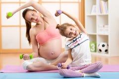 怀孕的母亲和她女儿儿童做 免版税库存照片