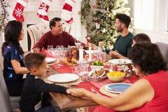 与祖父母的家庭说雍容在圣诞节膳食前 免版税库存照片
