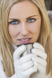 手套的白肤金发的妇女喝温暖的饮料的 库存照片