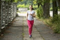 在跑步期间,年轻人炫耀女孩 夏天 库存照片