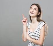 美丽的少妇画象逗人喜爱的嫩纯净的微笑的摆在的灰色背景 免版税图库摄影