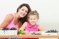 女儿帮助的家庭作业妈妈 库存照片
