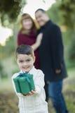 Λατρευτό μικτό αγόρι φυλών που δίνει το δώρο μπροστά από τους γονείς Στοκ φωτογραφία με δικαίωμα ελεύθερης χρήσης