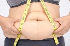 测量她的腹部油脂的妇女的手指 图库摄影