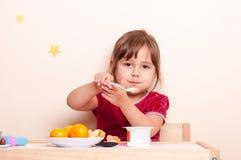 Μικρό κορίτσι που μοιράζεται τα φρούτα και το γιαούρτι Στοκ φωτογραφία με δικαίωμα ελεύθερης χρήσης