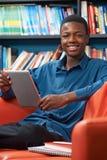 使用数字式片剂的男性少年学生在图书馆 库存照片