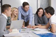 工作在有学生的教室的老师 免版税图库摄影