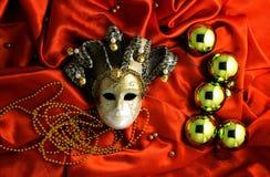 金黄圣诞树球和在红色发光的丝织物的金黄面具背景与金装饰的 免版税图库摄影