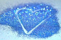 与蓝色闪烁闪闪发光的心脏的模糊的抽象背景蓝色表面上的 库存图片