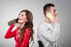 年轻夫妇谈话在手机 库存照片