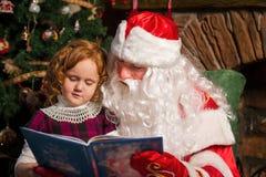 Βιβλίο ανάγνωσης Άγιου Βασίλη και μικρών κοριτσιών Στοκ Φωτογραφία