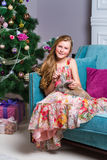 Όμορφη συνεδρίαση κοριτσιών μπροστά από ένα χριστουγεννιάτικο δέντρο Στοκ εικόνες με δικαίωμα ελεύθερης χρήσης
