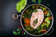 烹调在与菜的蒸汽鲑鱼排 免版税库存图片