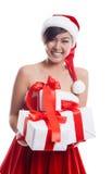 举行圣诞节礼物微笑的圣诞老人帽子圣诞节亚裔妇女 免版税库存照片