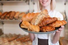 快乐的女性面包师提出新鲜面包 免版税库存照片