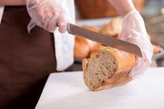 纯熟女性面包师为她的顾客服务 免版税库存照片