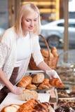 可爱的女性面包师卖甜酥皮点心 免版税库存照片