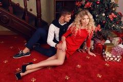 在典雅的衣裳的嫩夫妇,坐在圣诞树旁边在舒适家 免版税库存图片