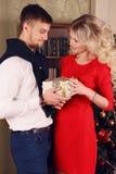 在典雅的衣裳的嫩夫妇,摆在圣诞树旁边在舒适家 免版税库存照片